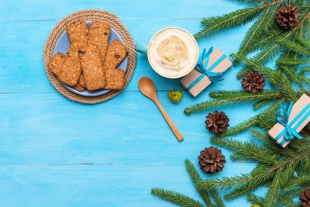 Kerstkoekjes met een drankje en cadeautjes, een groene boom met kegels op blauw. plat leggen