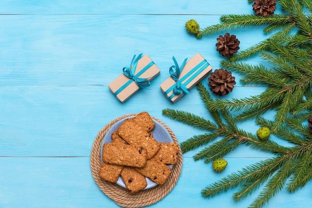 Kerstkoekjes met geschenken en een groene boom met kegels op een lichtblauwe achtergrond.