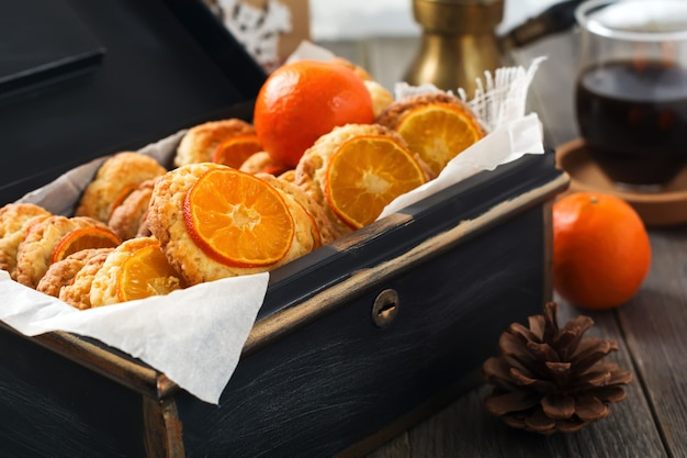 Kerstkoekjes met gesneden mandarijnen en kerstmisspeelgoed in een donkere doos. selectieve aandacht.