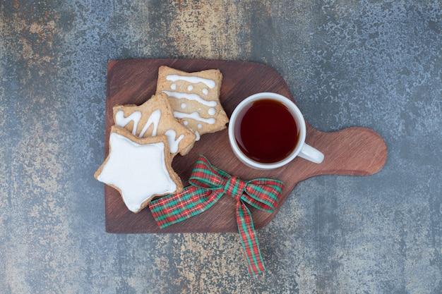 Kerstkoekjes met kopje thee op een houten bord