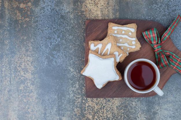 Kerstkoekjes met kopje thee op houten bord
