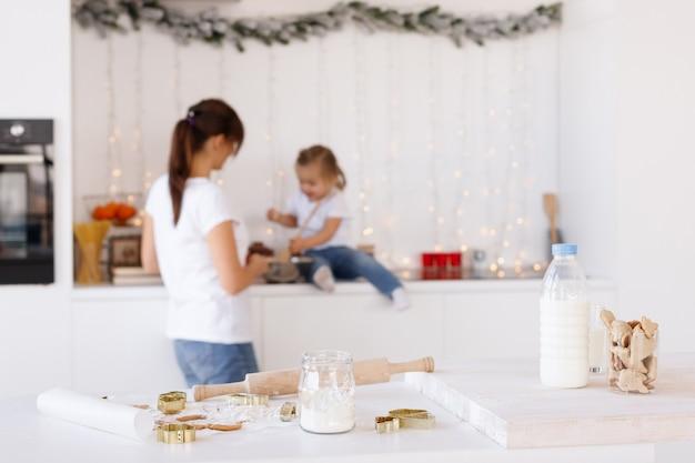 Kerstkoekjes met melk op tafel in de keuken moeder en dochter