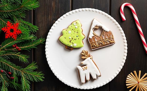 Kerstkoekjes op een bord op donkere houten achtergrond