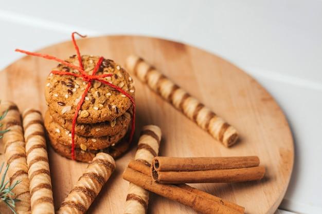 Kerstkoekjes, snoep en kaneelstokjes op een houten snijplank