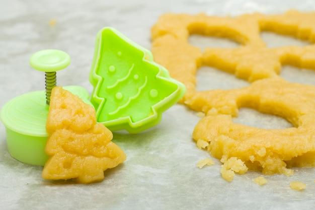 Kerstkoekjes voor kinderen. ruwe deeg en vormspar voor voorbereidingscookie. nieuwe ye