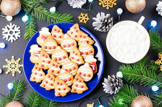 Kerstkoekjes, warme drank met marshmallows en decoraties met kerstboom en lampjes op zwart.
