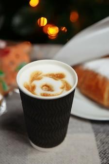 Kerstkoffie en croissants met geschenken en speelgoed op de achtergrond van de kerstboom