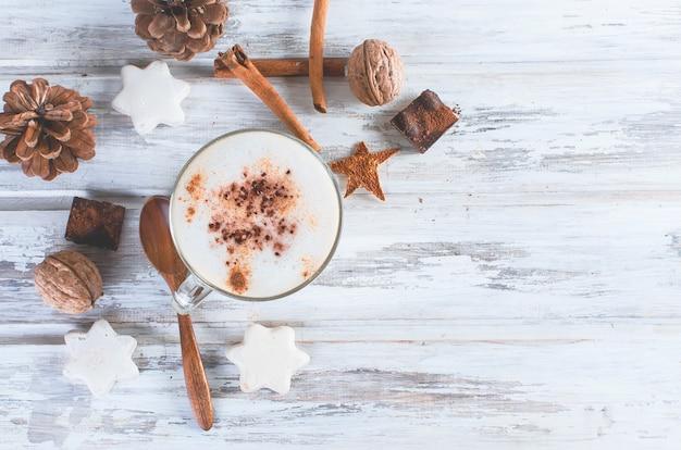 Kerstkoffie met melk, specerijen of warme chocolademelk, dennenappels