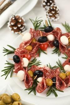 Kerstkrans - antipasto. salami-canapés met olijven, babymozzarella.