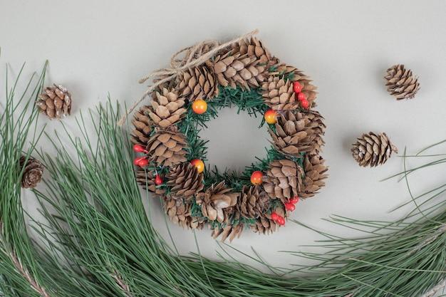 Kerstkrans en dennenappels op beige oppervlak