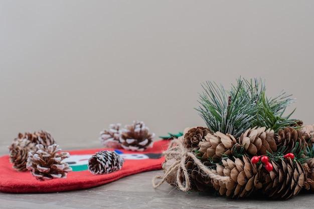 Kerstkrans en dennenappels op marmer.