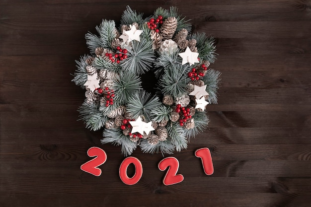 Kerstkrans en inscriptie 2021 peperkoekkoekje op houten achtergrond.