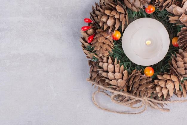 Kerstkrans en kaars op witte tafel.