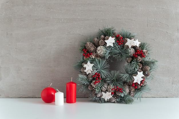 Kerstkrans en kaarsen op grijze achtergrond. gezellige decoraties voor de feestdagen.