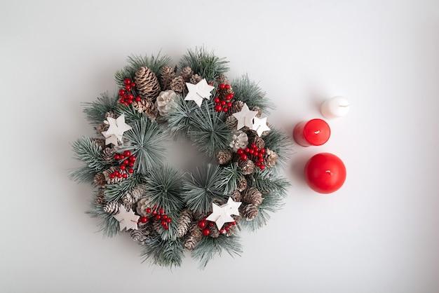 Kerstkrans en kaarsen op witte achtergrond bovenaanzicht. new years decoraties. kopieer ruimte.
