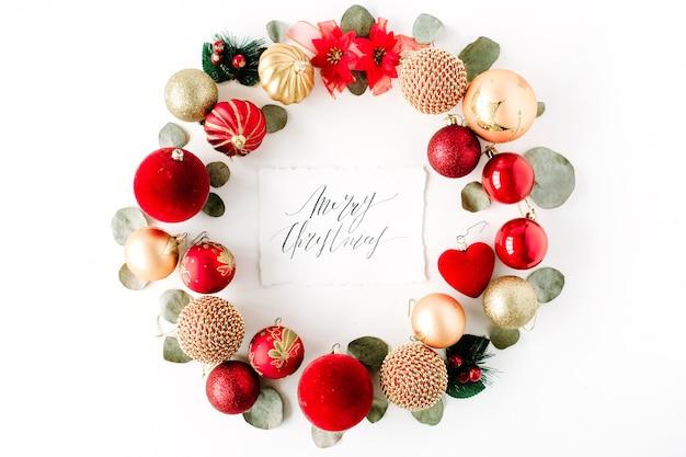 Kerstkrans frame gemaakt van gekleurde heldere kerstballen en kalligrafie woorden vrolijk kerstfeest op witte achtergrond.