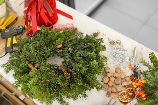 Kerstkrans gemaakt door professionele bloemist op tafel in bloemenwinkel