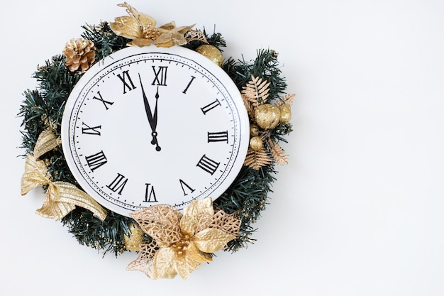 Kerstkrans gemaakt van dennentakken, gouden speelgoed en binnen de klok, gelukkig nieuwjaar