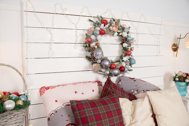 Kerstkrans gemaakt van dennentakken, kegels en kerstspeelgoed aan de muur. warm gezellig modern design