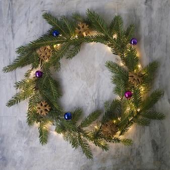 Kerstkrans gemaakt van dennentakken, koekjes, gekleurde ballen en gloeiende lichten.