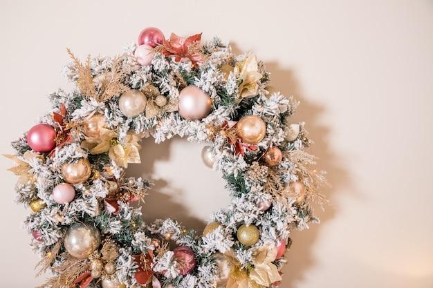 Kerstkrans gemaakt van natuurlijke fir takken opknoping op een beige muur.