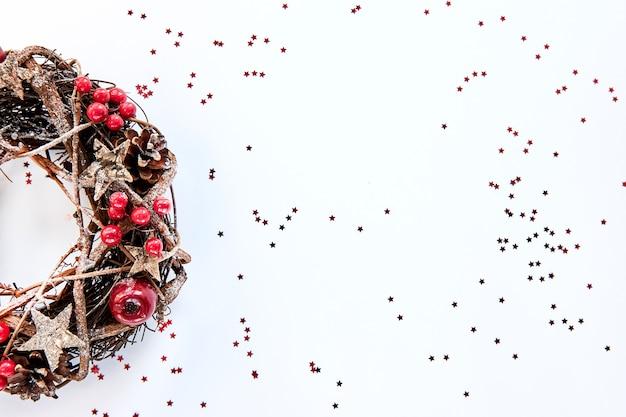Kerstkrans gemaakt van takken versierd met gouden houten sterren en rode bessen bubbels op een witte achtergrond