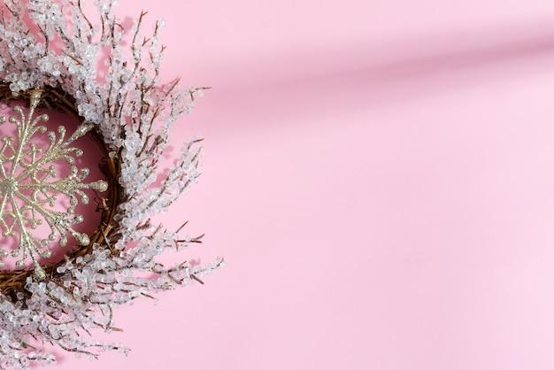 Kerstkrans handgemaakt in de vorm van creatieve sneeuwvlok op pastelroze. plat leggen