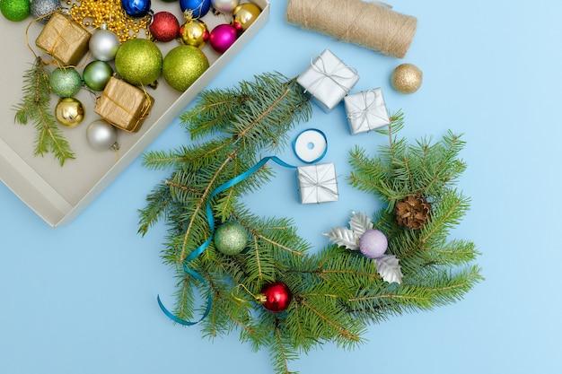 Kerstkrans maken. kerstballen, lint en dozen. blauwe achtergrond.