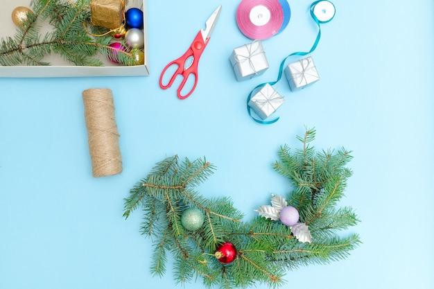 Kerstkrans maken. vuren tak, ornamenten, schaar. blauwe achtergrond.