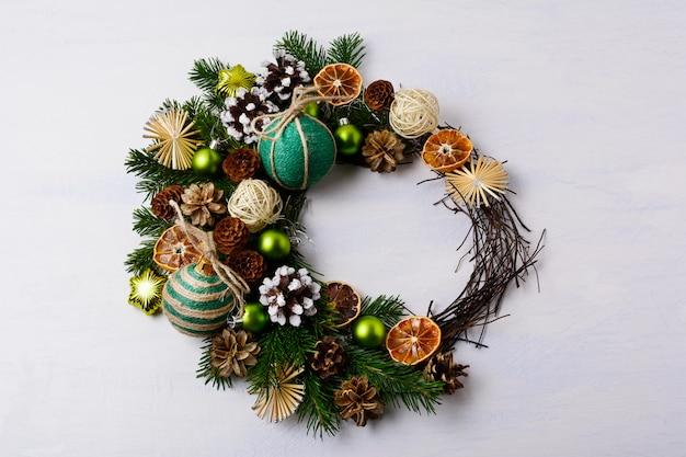 Kerstkrans met besneeuwde dennenappels en rustieke ornamenten