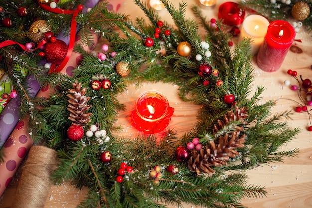 Kerstkrans met brandende kaars in het midden en versieringen op tafel