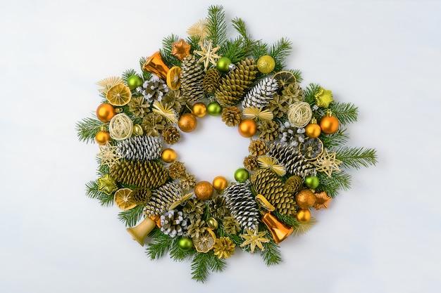Kerstkrans met dennentakken, dennenappels en gouden ornamenten