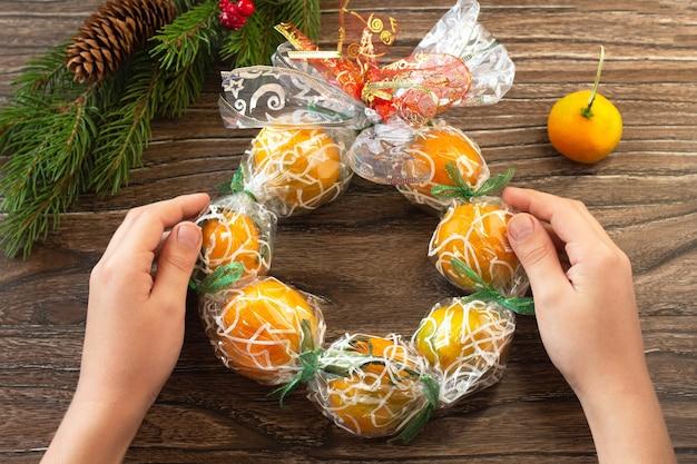 Kerstkrans met mandarijnen. handgemaakt. het project van de creativiteit van kinderen, knutselen, knutselen voor kinderen.
