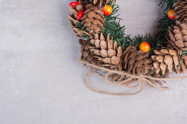 Kerstkrans met rode kralen op witte tafel.