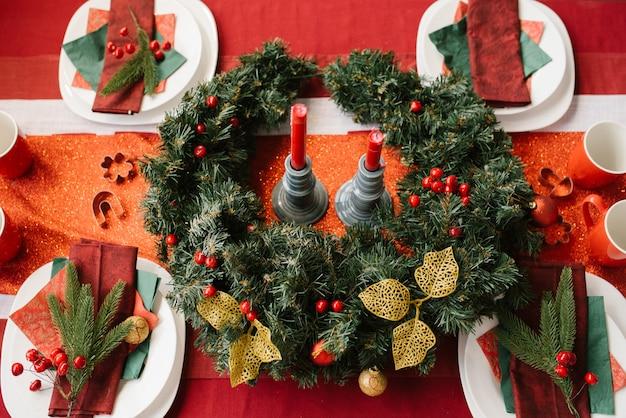Kerstkrans op de feestelijke tafel, geserveerd voor een feestelijk diner