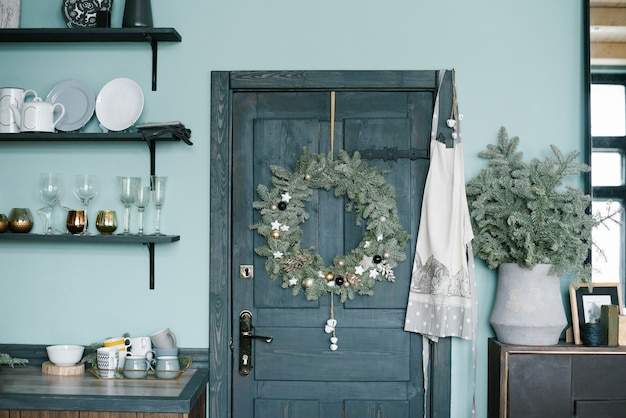 Kerstkrans op de houten deur in de keuken in scandinavische stijl in blauwe tinten