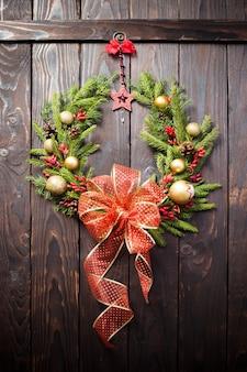 Kerstkrans op donkere houten deur
