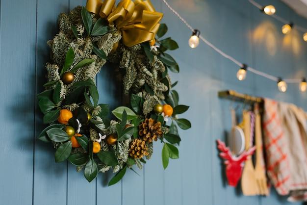 Kerstkrans opknoping op blauwe ergernis muur met verlichting erop, decor appartement of keuken in het huis