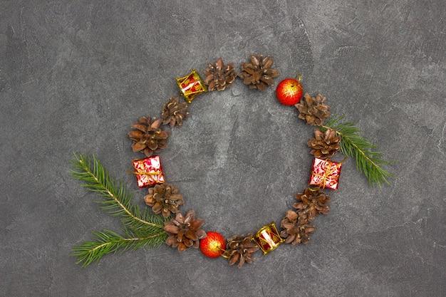 Kerstkrans van dennenappels, takken en rood speelgoed. zwarte achtergrond. kopieer ruimte. plat leggen