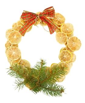 Kerstkrans van gedroogde citroenen met dennenboom en boog geïsoleerd op wit