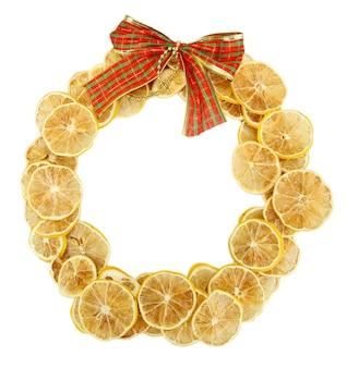 Kerstkrans van gedroogde citroenen met strik op wit wordt geïsoleerd