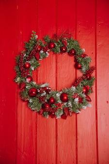 Kerstkrans van pijnboomtakken met kaarsen op een rode houten achtergrond, kerstballen, kopie ruimte