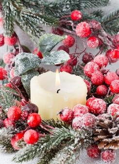 Kerstkrans van rode bessen, een bontboom en kegels