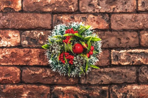Kerstkrans van sparren en appels op een rode bakstenen muur.