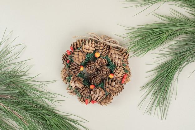 Kerstkrans versierd met dennenappels en hulst bessen