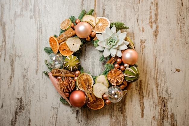 Kerstkrans versierd met gedroogde sinaasappels, kaneelstokjes, vetplanten en boomspeelgoed