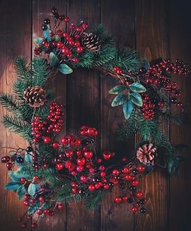 Kerstkransdecoratie met dennenappels en meidoornbessen op houten oppervlak