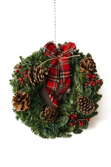 Kerstkroon en winter krans decoratie met hulst, maretak, spar, blauwe spar, dennenappels op witte achtergrond.