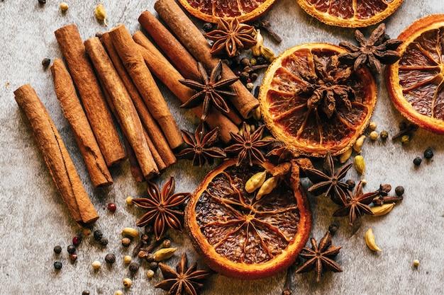 Kerstkruid. kaneel, gedroogde sinaasappelen en anijs op een grijze tafel.
