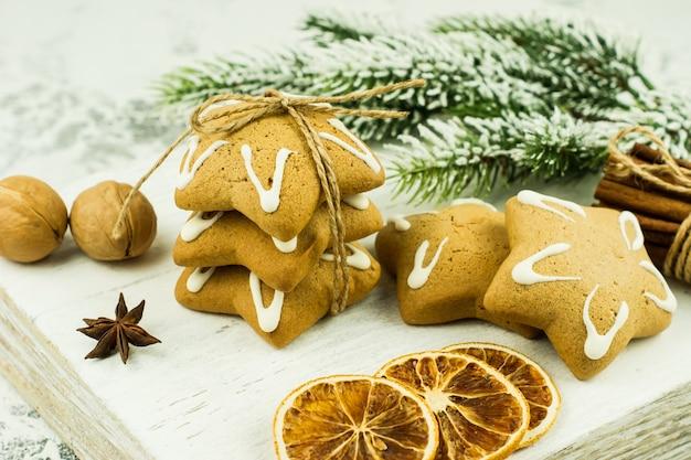 Kerstkruiden, peperkoekkoekjes en bakingrediënten op witte achtergrond. kaneel, anijssterren, walnoten, kruidnagel voor kerstkoekjes.